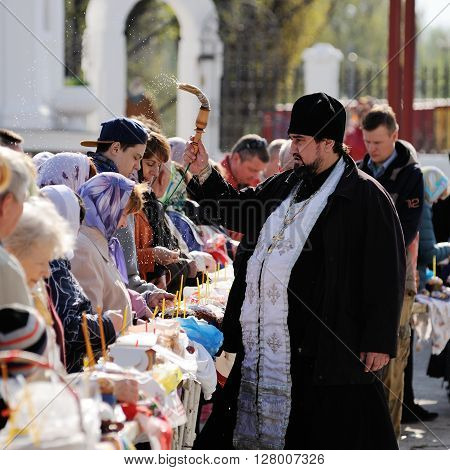 Orel Russia - April 30 2016: Paschal blessing of Easter baskets in Orthodox church. Priest sprinkling holy water on people and kulichi closeup