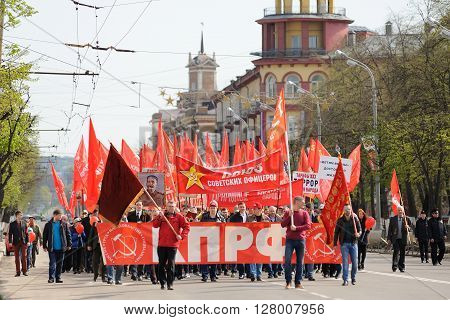 Orel Russia - May 1 2016: Communist party demonstration. People marching with red flags on empty street horizontal