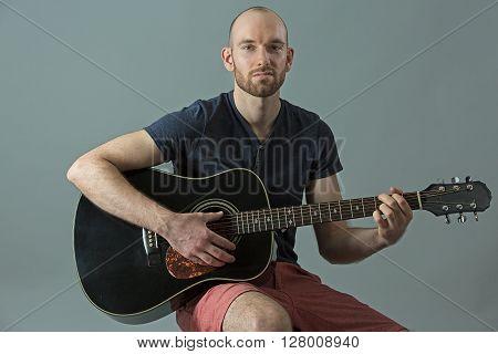 Young guitarist man playing an acoustic guitar
