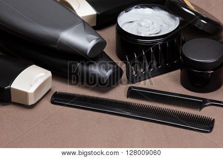 Different hair care and styling products and accessories. Cosmetics and various kinds of combs on brown textured surface