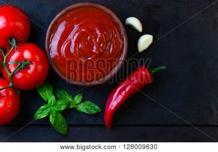 Tomato sauce salsa and ingredients - tomatoes, garlic, chili on dark stone background. Top view