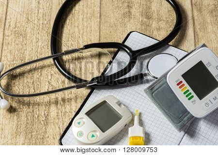 Stethoskope on wooden desk with blood pressure measurement