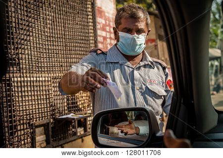 MADURAI, INDIA - JANUARY 29 2014: A car parking attendant wearing a face mask issuing a ticket at a public car park in Madurai.