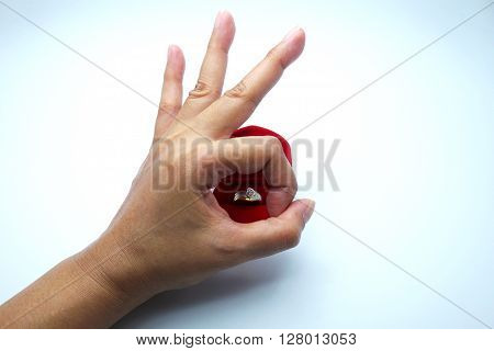 A valentine prop, woman hand in OK sign with diamond ring in heart shape on ring box in OK sign on white-gray background. Focus on ring.