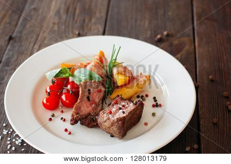Medium rare pork steak with fresh vegetables on white plate. Top view food photography of pork steak with potatoes and tomatoes cherry. Prepared meat with vegetables on dark wooden background.
