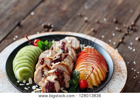Food photography of baked veal with fresh fruits on wooden background. Baked meat with tropical fruits top view. Flat lay of creative food from baked veal on wooden table. ** Note: Shallow depth of field