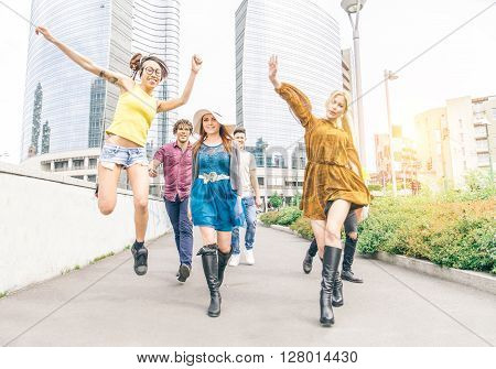 Group of happy friends walking and having fun in an urban area - Multi-ethnic group of young people jumping and dancing outdoors