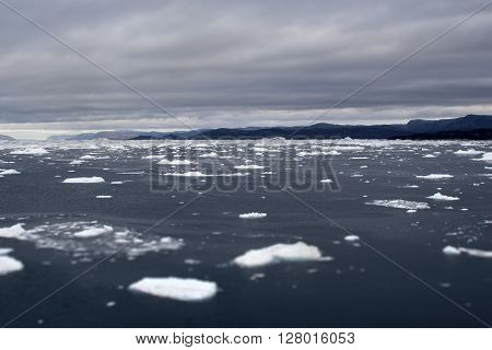 Greenland glaciers mountains ocean sky blue water