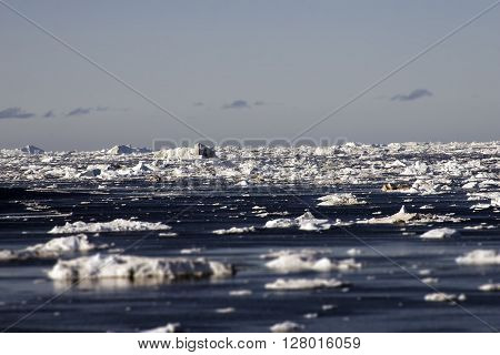 Greenland glaciers ocean sky clouds blue water