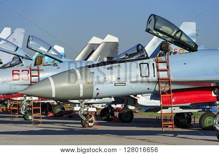 Fighter and bomber jets in row, military multifunction planes with open bulletproof cockpits and ladders for pilots, modern army industry, supersonic air force, blue sky on background, selective focus