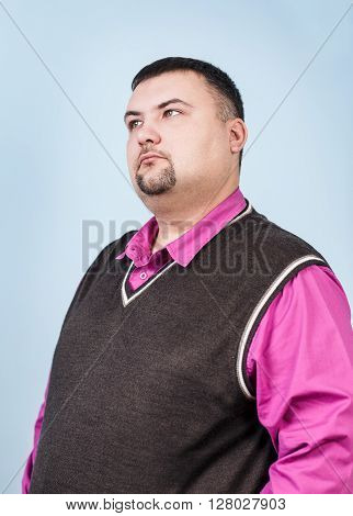 Thoughtful plump businessman on the blue background