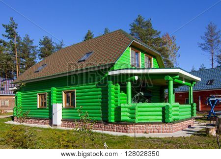 green a house made of wooden logs in the village against the blue sky