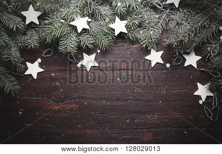 Christmas or New Year background: fur-tree branches, decoration and glittering stars on wooden background, top view, copy space.