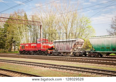 attached diesel locomotive is pulling freight wagons spring