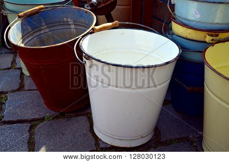 old, different colored buckets standing at the street