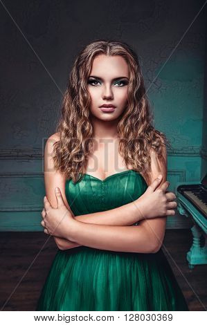 portrait of young beautiful girl in rich long green dress in luxury interior in photo studio