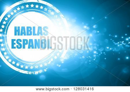 Blue stamp on a glittering background: hablas espanol
