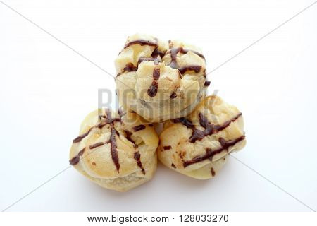 Eclair With Chocolate Topping On White Dish Over White Background, Free Copy Space