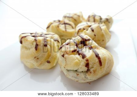 Eclair with chocolate topping on white dish over white background free copy space