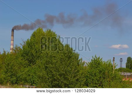 Factory with two industrial smoke stacks on nature in spring. Works stone pipes rising above green and yellow trees, industrial landscape photo. Non-smoking chimney-stalk against blue sky on sunny day