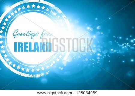 Blue stamp on a glittering background: Greetings from ireland