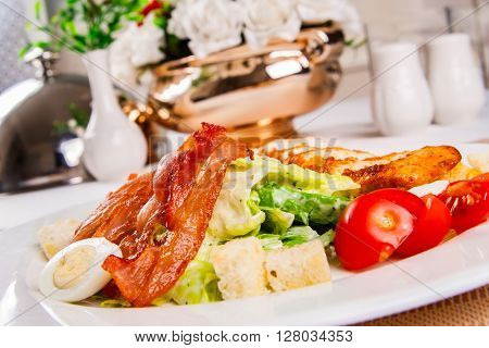Caesar salad with chicken and bacon on white plate