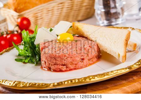 Beef tartare with bread on white plate