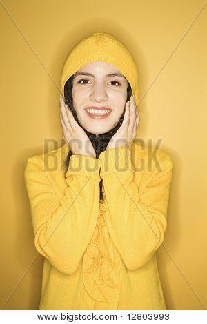 Sorridente jovens caucasianos mulher vestindo amarelo gabardine em fundo amarelo.