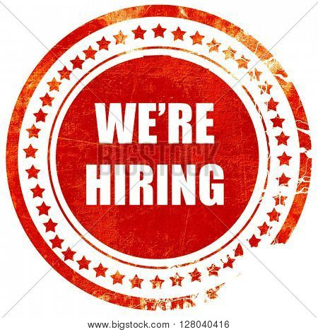 We are hiring sign, grunge red rubber stamp on a solid white bac