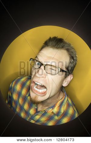 Vignette of adult Caucasian man on yellow background winking and making funny face.