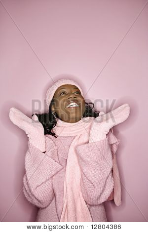 Portrait of smiling African-American mid-adult woman on pink background wearing winter coat, hat, and scarf looking upward.