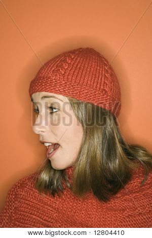 Side view of young adult Caucasian woman on orange background wearing winter hat and scarf.