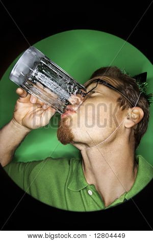 Vignette of adult Caucasian man on green background wearing green hat and drinking beer.