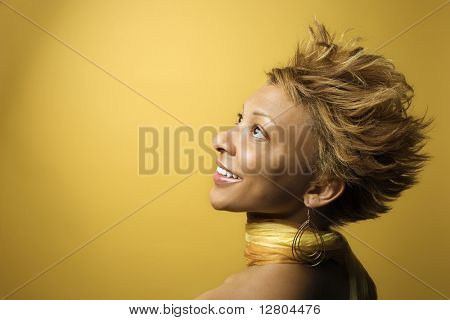 Side view portrait of smiling young African-American adult woman on yellow background.