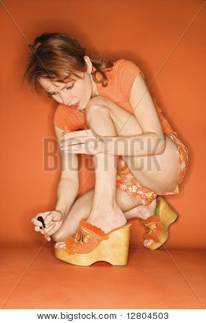 Caucasian mid-adult woman on orange background painting her toenails with nail polish.