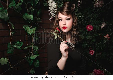 Magic portrait of romantic beautiful girl with wavy hair red lips black dress holding rose flower in blooming garden. Fashion Female fairy tale about princess walking mistery forest. Creative art concept in fantasy stylization.