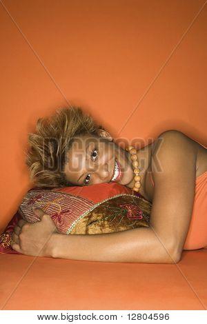 Porträt von lächelnd African-American young adult Woman auf orange Hintergrund mit Kopf am Boden liegen