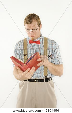 Caucasian young man dressed like nerd reading book.