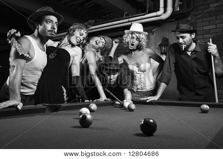 Group of Caucasian prime adult retro males and females trying to distract man as he takes pool shot.