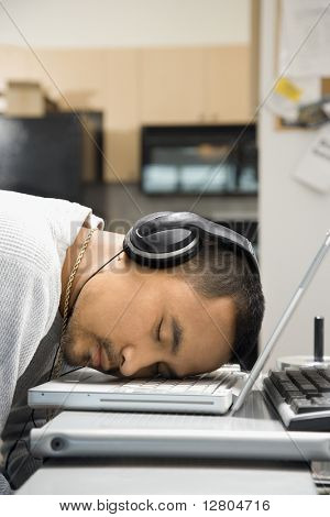 Close-up of Asian young adult man sleeping with head on laptop keyboard and wearing headphones.