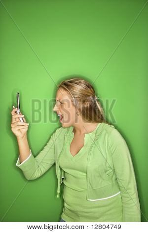 Portrait of blond Caucasian teen girl looking at cellphone with shock and disbelief against green background.