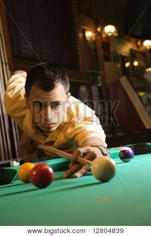 Young man concentrating while aiming at pool ball while playing billiards.