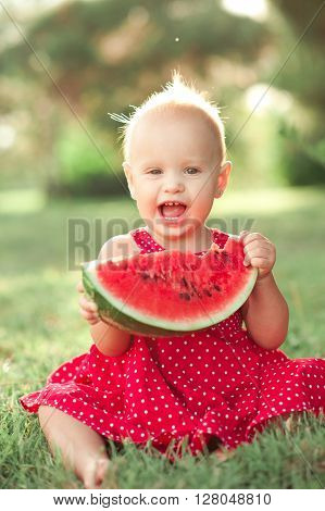 Funny baby girl eating watermelon outdoors. Laughing child. Looking at camera. Childhood.
