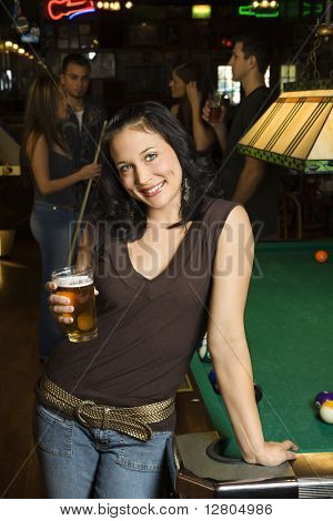 Portrait of young caucasian woman holding beer beside billiards table in pub.