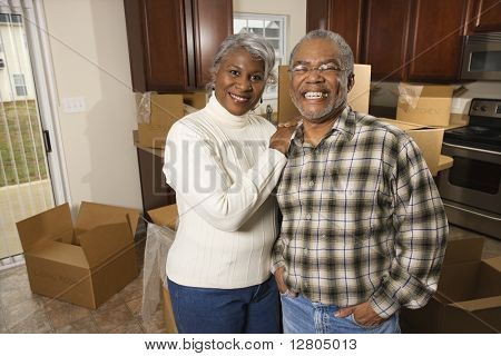 Portrait of middle-aged African-American couple in kitchen with moving boxes.