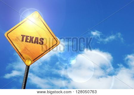 Yellow road sign with a blue sky and white clouds:  texas