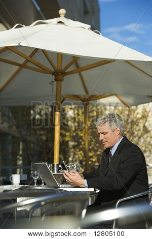 Prime adult Caucasian man in suit sitting at patio table outside with laptop and dialing cellphone.