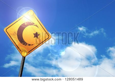 Yellow road sign with a blue sky and white clouds: Islam faith s