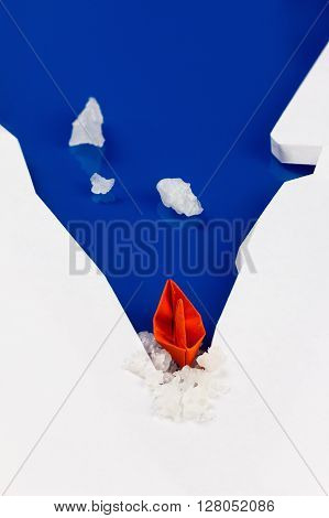 Origami paper boat on water as an icebreaker ice punched. Concept of success moving forward overcoming difficulties