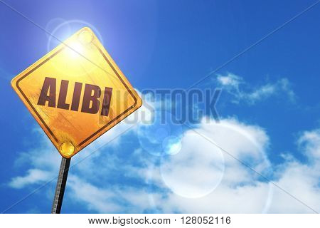 Yellow road sign with a blue sky and white clouds: alibi